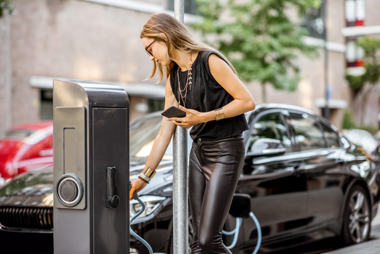 A lady using car charging on street